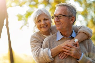 senior woman hugs her senior husband while smiling outside