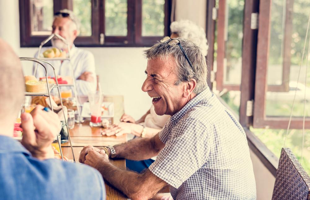 Seniors laughing and enjoying breakfast