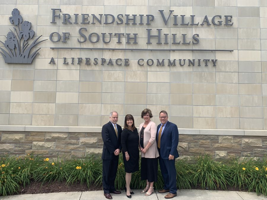 Team members of Friendship Village of South Hills posing in front of the community's name