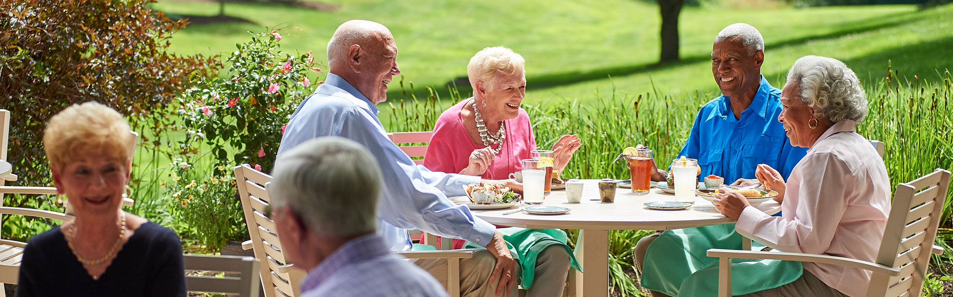 A group of residents at Friendship Village of South Hills sitting outside and enjoying a meal