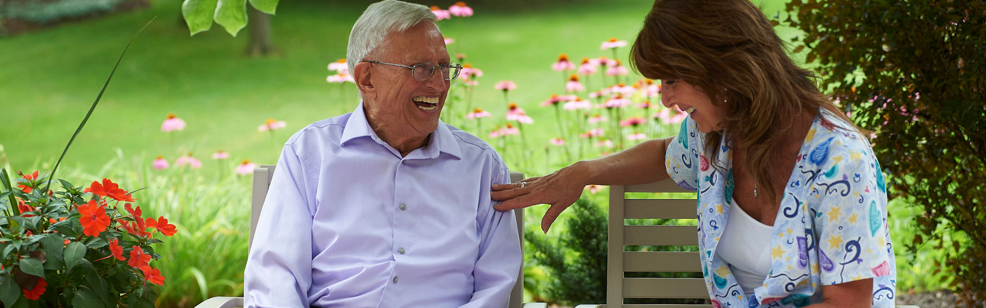 An elderly man sitting outside laughing and talking with a nurse