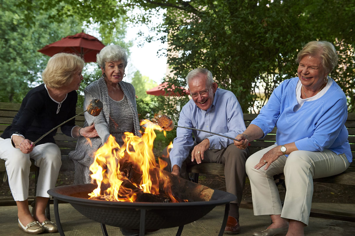 A group of residents at Friendship Village of South Hills sitting around a fire toasting marshmallows