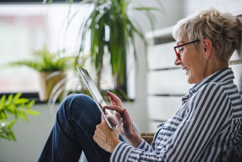senior woman browsing the web on her tablet while sitting down