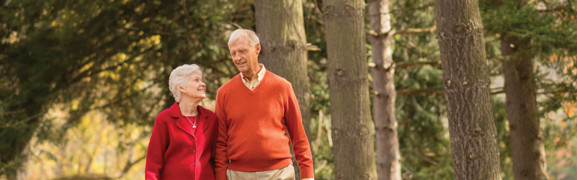 An elderly couple taking a walk in a wooded area