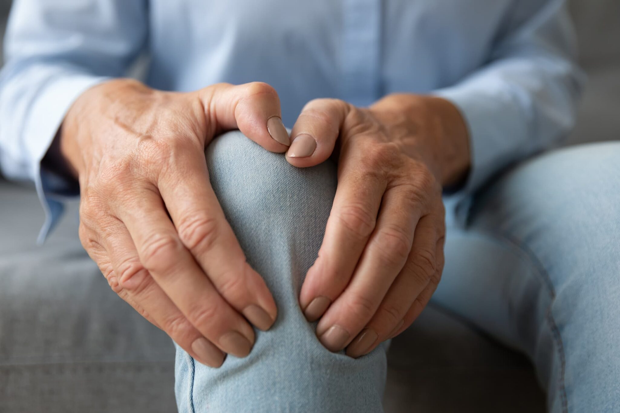 Older woman with hands on knee in pain.