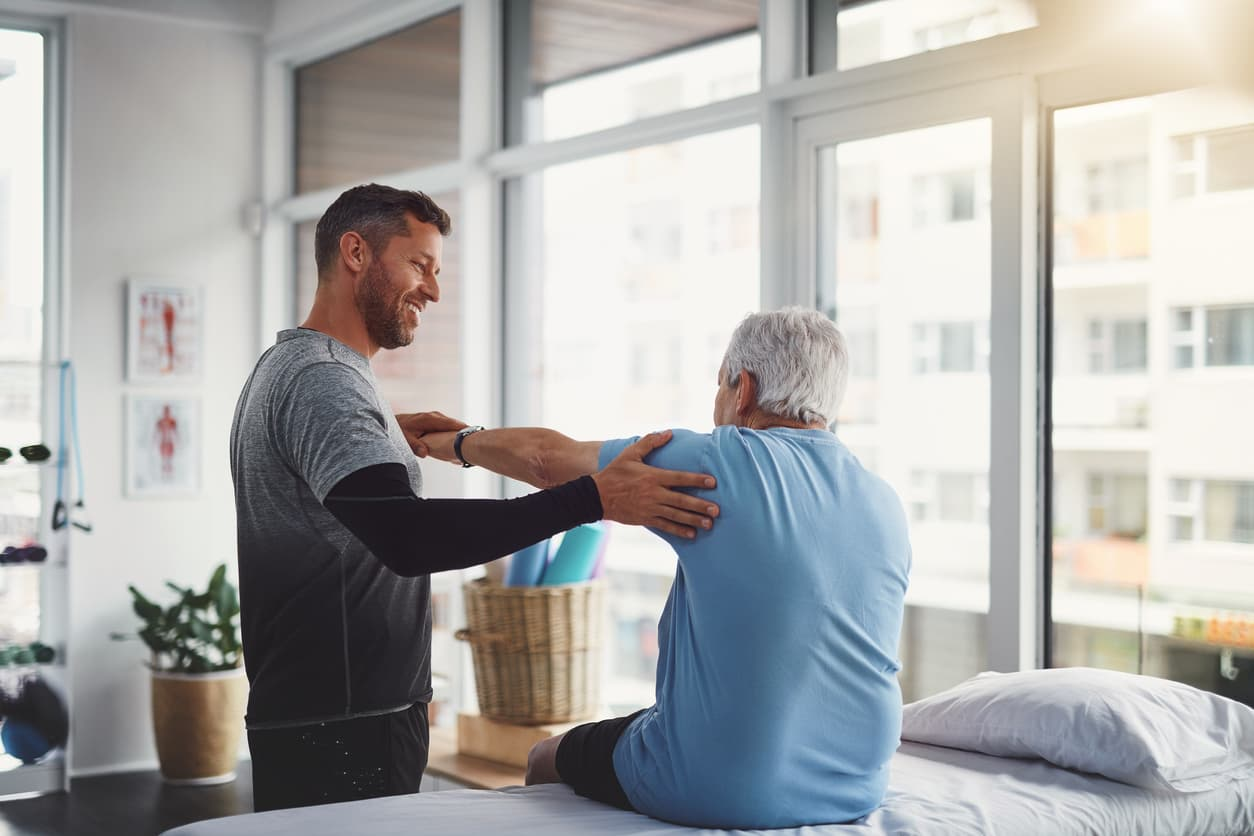 Young male physiotherapist assisting a senior patient in recovery.